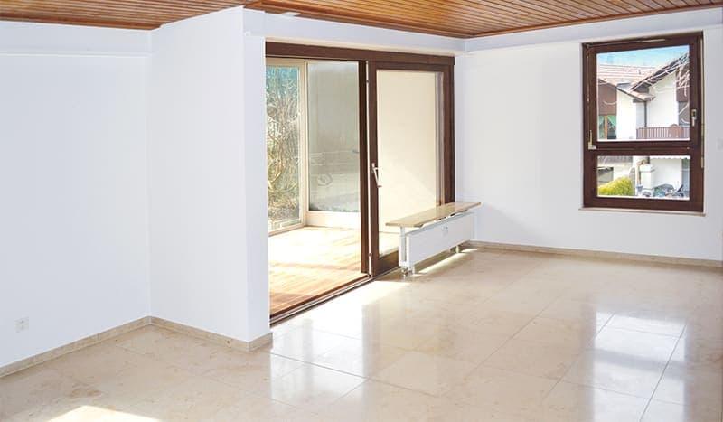 Wohnzimmer mit Natursteinboden. Wintergarten mit Parkett